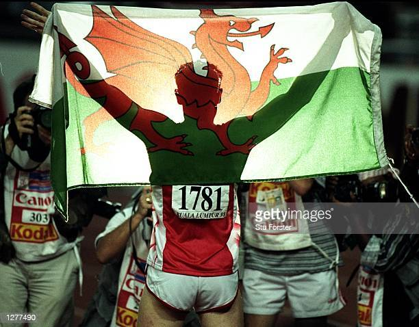 Iwan Thomas flies the flag for Wales after victory in the 400m during the Commonwealth Games in Kuala Lumpur, Malaysia. \ Mandatory Credit: Stu...