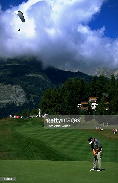 Lee Westwood of England putts a s a parapentiste floats above during the 1998 Canon European Masters played at the CranssurSierre Golf Club Crans...
