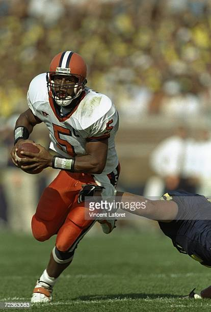 Quarterback Donovan McNabb of the Syracuse Orangeman grips the ball as he avoids being tackled during the game against Michigan Wolverines at...