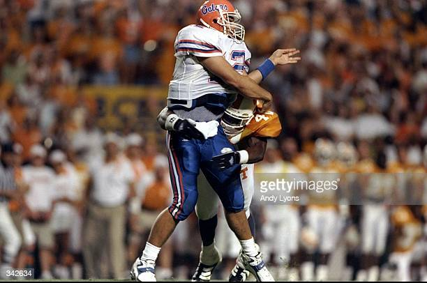 Quarterback Doug Johnson of the Florida Gators in action against defensive tackle Billy Ratliff of the Tennessee Volunteers during a game at the...