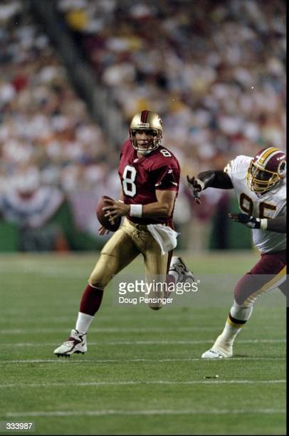Quarterback Steve Young of the San Francisco 49ers in action against defensive tackle Dan Wilkinson of the Washington Redskins during the game at the...