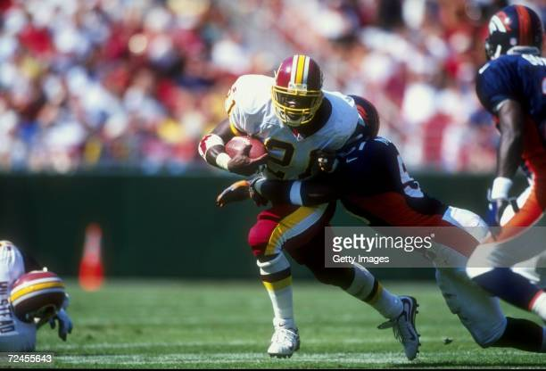 Running back Terry Allen of the Washington Redskins in action against linebacker John Mobley of the Denver Broncos during the game at the Jack Kent...