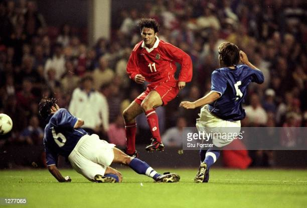 Ryan Giggs of Wales shoots between two Italian defenders during the European Championship qualifier at Anfield in Liverpool England Italy won 20...