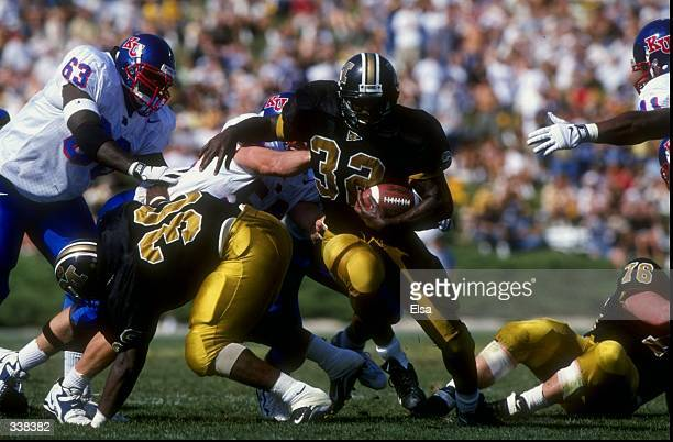 Tailback Devin West of the Missouri Tigers in action against defensive end Dion Johnson of the Kansas Jayhawks during a game at Faurot Field in...