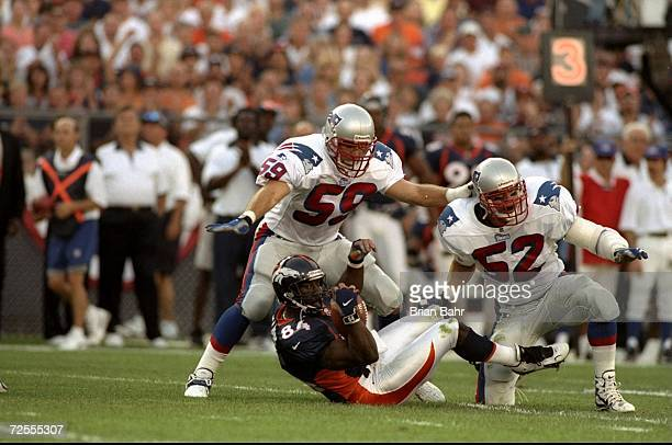 Tight end Shannon Sharpe of the Denver Broncos in action against linebackers Todd Collins and Ted Johnson of the New England Patriots during the game...