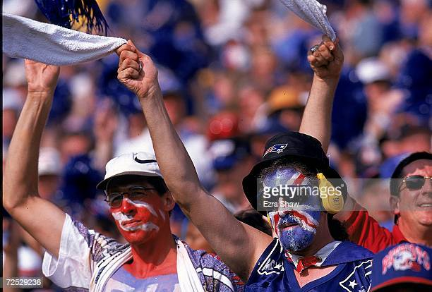 Two New England Patriots fans with painted faces cheer in the stands during a game against the Tennessee Oilers at the Foxboro Stadium in Foxboro...