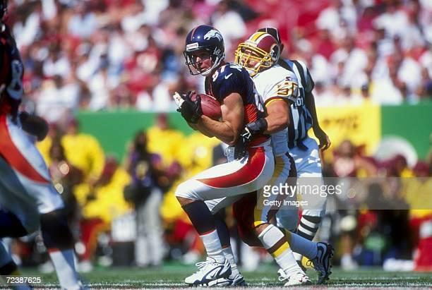 Wide receiver Ed McCaffrey of the Denver Broncos in action against linebacker Derek Smith of the Washington Redskins during the game at the Jack Kent...
