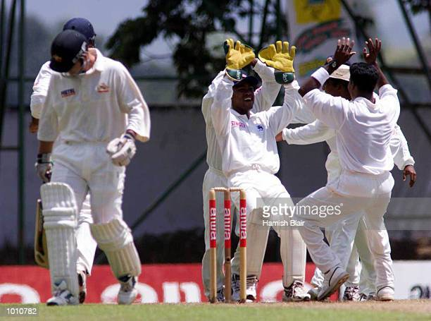Disappointed Justin Langer of Australia walks to the dressing room as the Sri Lankans celebrate his wicket, during day one of the First Test between...