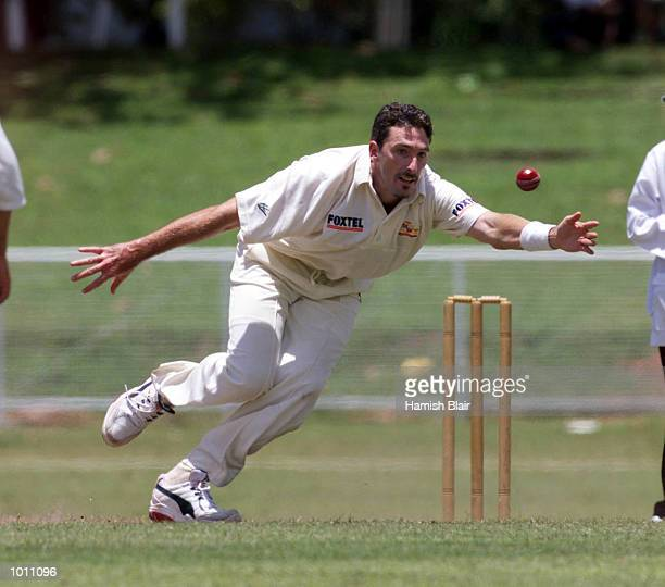 Damien Fleming of Australia lunges to field off his own bowling during day three of the Tour match between the Sri Lanka Board XI and Australia at...