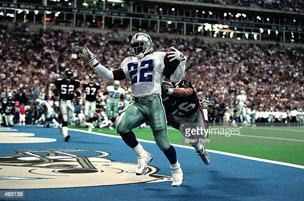 Emmitt Smith of the Dallas Cowboys makes a touchdown as he is hit by Mike Brookings of the Atlanta Falcons at the Texas Stadium in Irving Texas The...