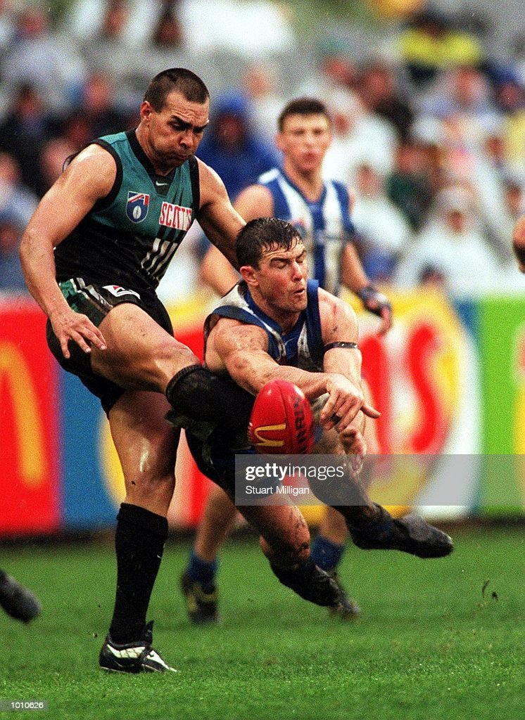 Fabian Francis,#8 for Port Adelaide attempts to kick the ball as Anthony Stevens#10 for the Kangaroos smothers the kick, during the Third Qualifying Final played between the Kangaroos and Port Adelaide played at the M.C.G, Melbourne, Australia. Mandatory Credit: Stuart Milligan/ALLSPORT