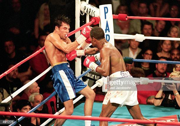 Felix Trinidad knocks Oscar De La Hoya back into the ropes during the welterweight title fight at the Mandalay Bay Casino in Las Vegas Nevada...