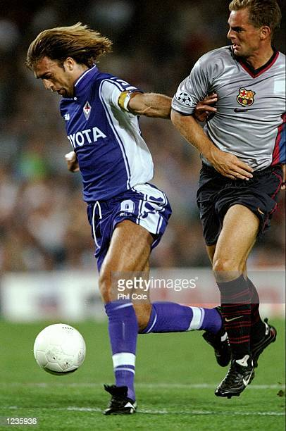 Gabriele Batistuta of Fiorentina beats Ronald de Boer of Barcelona during the UEFA Champions League group B match at the Nou Camp in Barcelona Spain...