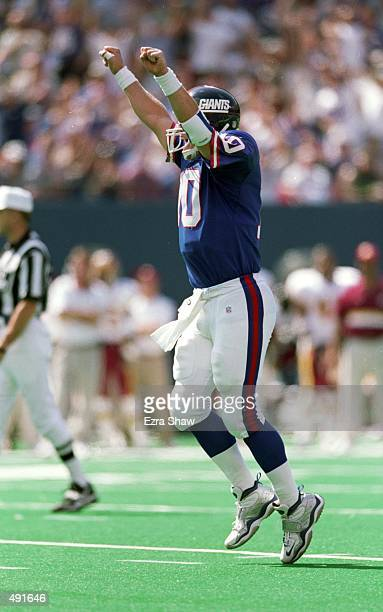 Kent Graham of the New York Giants celebrates on the field during a game against the Washington Redskins at the Giants Stadium in East Rutherford New...
