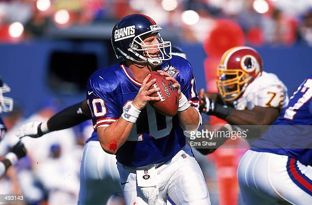 Kent Graham of the New York Giants moves back to pass during the game against the Washington Redskins at Giants Stadium in East Rutherford New Jersey...