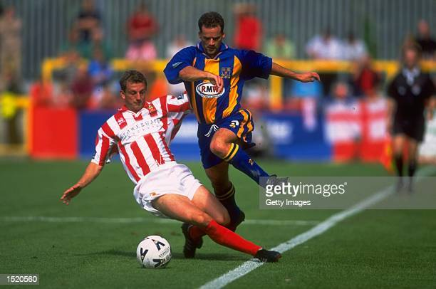 Kevin Seabury of Shrewsbury Town skips past Lee Howells of Cheltenham Town during the Nationwide Division Three match played at Whaddon Road in...
