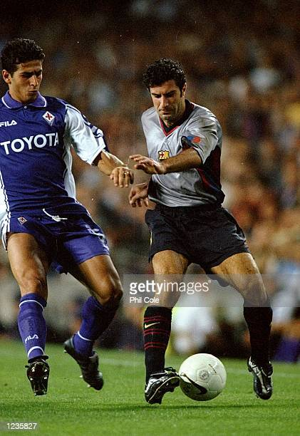 Luis Figo of Barcelona takes on of Pasquale Padalino of Fiorentina during the UEFA Champions League group B match at the Nou Camp in Barcelona Spain...