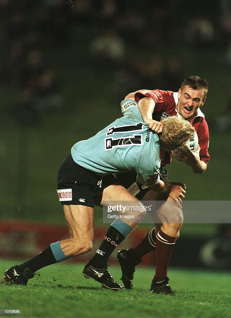 Matt Dowling of the NSW Waratahs (left) tackles of Chris Latham of the Queensland Reds during the National Ricoh Championship game at Ballymore, Brisbane, Australia. Mandatory Credit: Allsport Aus/ALLSPORT