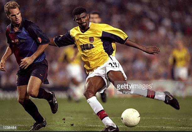 Nwankwo Kanu of Arsenal is shadowed by Frank de Boer of Barcelona during the Barcelona v Arsenal UEFA Champions League Group B match played at the...