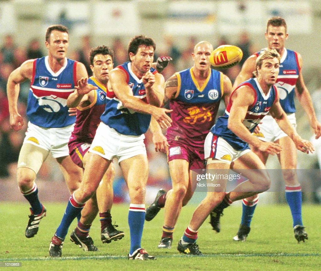 Paul Hudson #9 for the Western Bulldogs hand passes, as Chris Scott #22 for the Brisbane Lions is in pursuit during the 2nd semi final between the Brisbane Lions and the Western Bulldogs at the Gabba, Brisbane, Australia. Mandatory Credit:Nick Wilson/ALLSPORT