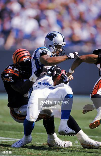 Rae Carruth of the Cincinnati Bengals carries the ball as he is tackled during the game against the Carolina Panthers at the Ericson Stadium in...