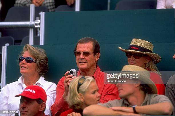 Roger Moore enjoys the action during the Canon European Masters at CranssurSierre in Switzerland Mandatory Credit David Cannon /Allsport