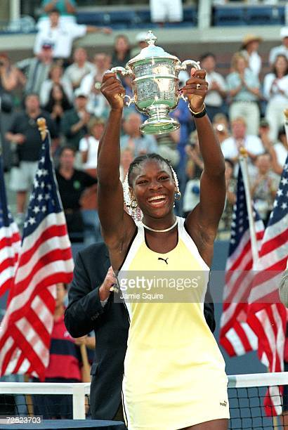 Serena Williams smiles and poses with her trophy after winning the US Open at the USTA National Tennis Courts in Flushing Meadows, New York.