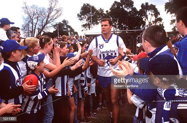 Wayne Carey captain of the Kangaroos is cheered onto the ground by fans during the Kangaroos final training session before their grand final game...