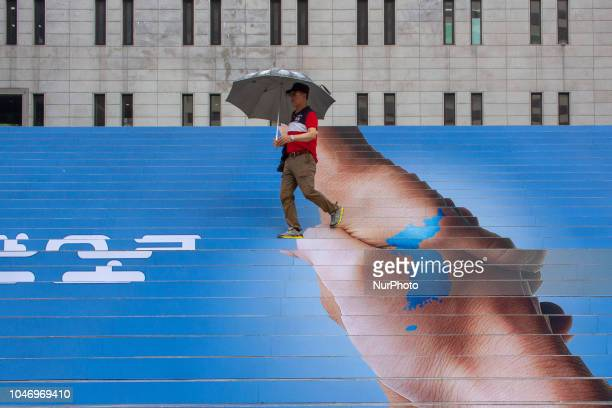 Sep 20 2018Seoul South KoreaA people passes by an image of two hands shaking to form the shape of the Korean Peninsula to mark the interKorean summit...