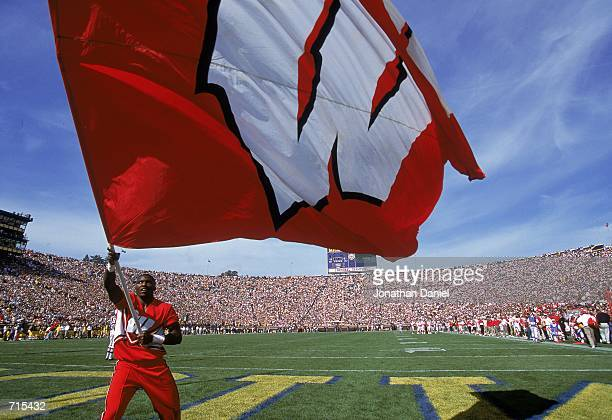 A cheeleader of the Wisconsin Badgers waves a huge flag on the sidelines during a game against the Michigan Wolverines at the Michigan Stadium in Ann...