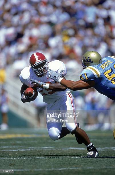 Ahmaad Galloway of the Alabama Crimson Tide runs with the ball while Tony White reaches to tackle him during the game against the UCLA Bruins at the...