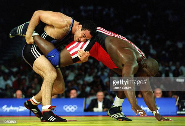 Alexis Rodriguez of Cuba is held by Krassimir Kotchev of Bulgaria during the 130 kilogram Freestyle wrestling event held at the Sydney Convention and...