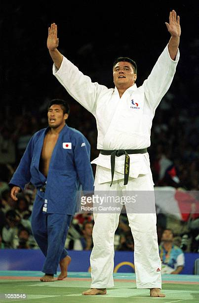 David Douillet of France celebrates winning the gold medal in the mens Heavyweight Judo event as a dejected Shinichi Shinohara of Japan claims the...