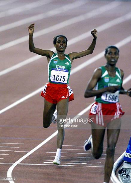 Derartu Tulu of Ethiopia celebrates as she crosses the line to take Gold in the final of the Women's 10000m at the Sydney 2000 Olympic Games held at...