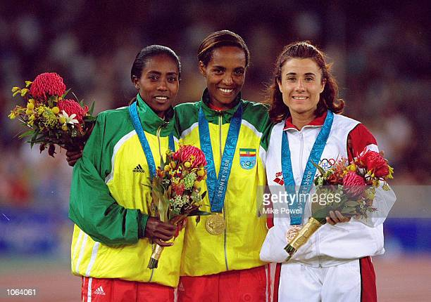 Derartu Tulu of Ethiopia on the podium after winning gold in the Womens 10000m Final alongside silver medallist Gete Wami also of Ethiopia and bronze...