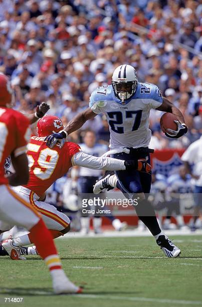 Eddie George of the Tennessee Titans leaps out of the way from Donnie Edwards of the Kansas City Chiefs during the game at the Adelphia Stadium in...