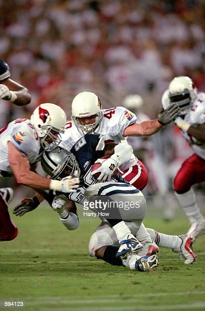 Emmitt Smith of the Dallas Cowboys carries the ball as he is tackled by Pat Tillman and Rob Freddrickson of the Arizona Cardinals at the Sun Devil...
