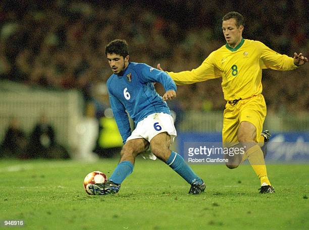 Gennaro Gattuso of Italy holds the ball up against Lucas Neill during the Sydney 2000 Men's Olympic football tournament Group A match played at the...