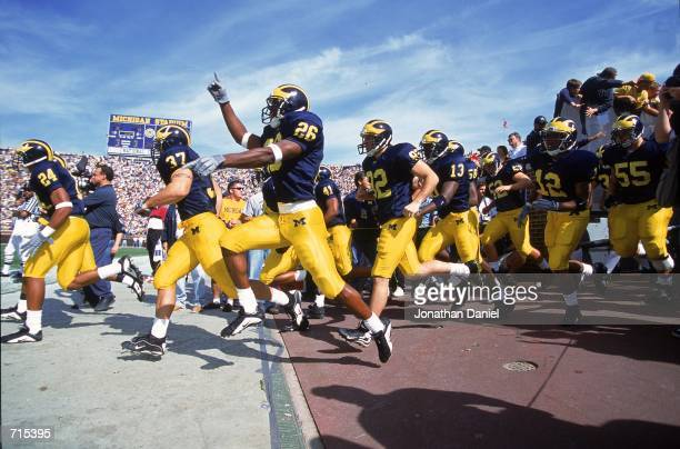 Julius Curry of the Michigan Wolverines leads the cheers as the team runs out to the field before the game against the Wisconsin Badgers at the...