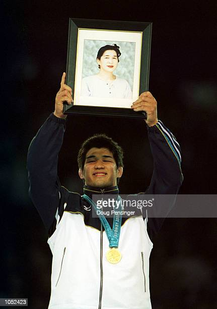 Kosei Inoue of Japan shows a picture of his recently deceased Mother as he celebrates winning the gold medal in the mens 100 kilogram Judo event at...