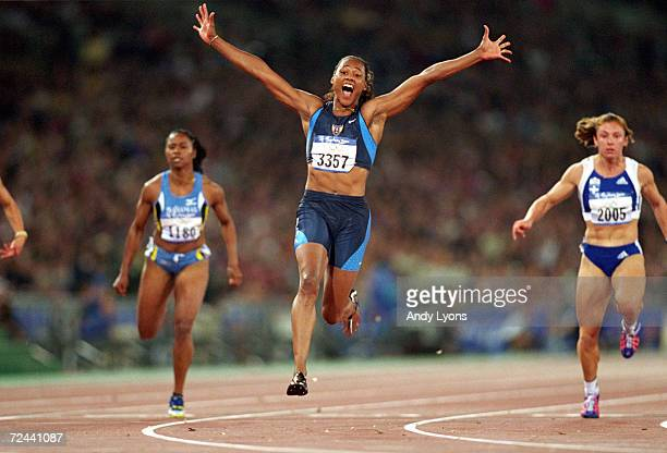 Marion Jones of the USA celebrates winning Gold in the Womens 100m Final at the Olympic Stadium on Day Eight of the Sydney 2000 Olympic Games in...