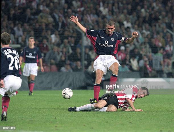 Mark Van Bommel of PSV Eindhoven slides into Roy Keane of Manchester United during the UEFA Champions League Group G match at the Philips Stadion in...