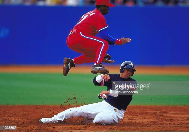 Norihiro Nakamura of Japan slides in on German Mesa of Cuba in the Mens Baseball Semifinal at the Baseball Stadium in the Olympic Park on Day 11 of...