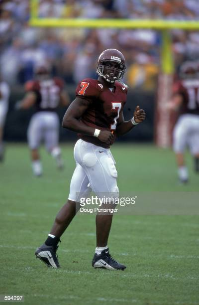 Quarterback Michael Vick of the Virginia Tech Hokies jogs on the field during a game against the Akron Zips at Lane Stadium in Blackburg Virginia The...