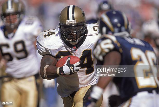Ricky Williams of the New Orleans Saints races by Darryl Lewis of the San Diego Chargers to make a touchdown during the game at Qualcomm Stadium in...