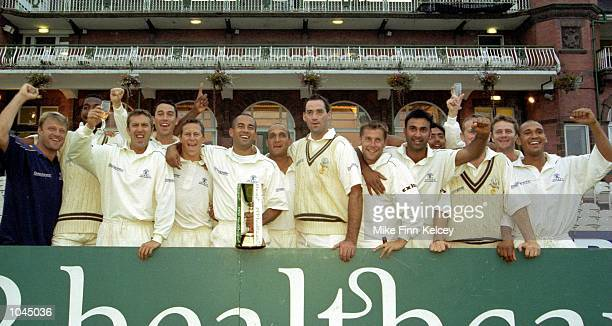 Surrey players, led by captain Adam Hollioake , celebrate winning the PPP Healthcare County Championship match between Lancashire and Surrey played...