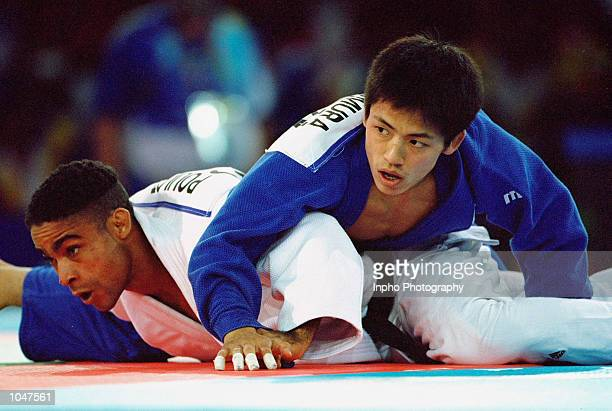 Tadahiro Nomura of Japan pins down Manolo Poulot of Cuba in the Men's 60kg Judo event at the Exhibition Halls in Darling Harbour on Day Two of the...