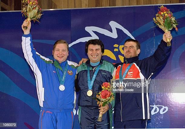 Tanyu Kiriakov of Bulgaria on the podium after winning gold in the Men's 50m Pistol Shooting event alongside silver medallist Igor Basinsky of...