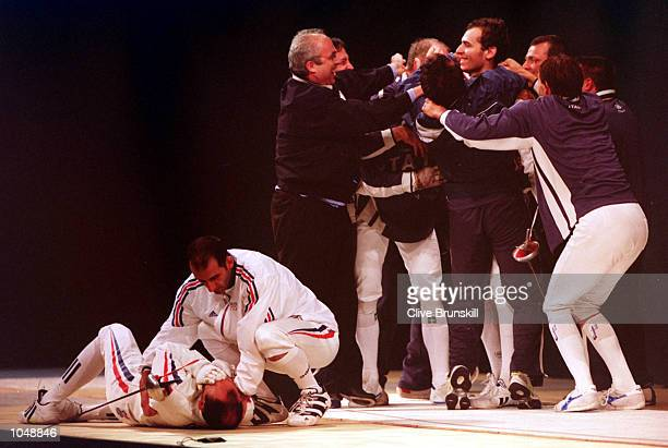 The Italian celebrate victory over France as Hugues Obry of France is consoled on the floor in the Mens Team Epee Fencing gold medal match at the...