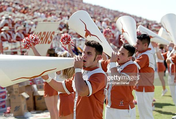 The Texas Longhorns cheerleaders yell into megaphones on the sidelines during a game against the Oklahoma State Cowboys at the RoyalMemorial Stadium...